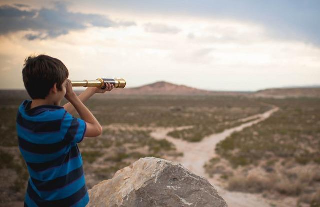 boy-looking-through-telescope-in-desert