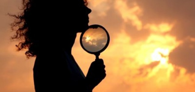 stock-footage-woman-holds-magnifier-and-puts-it-to-chin-against-sky-and-sun-720x340